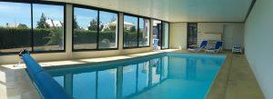 La piscine intérieure de la Villa Belle Île avec transats