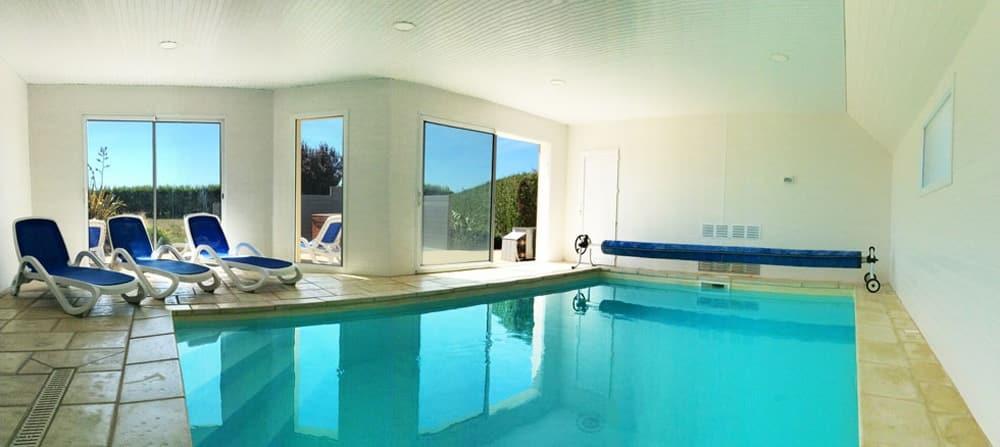 La piscine intérieure de la Villa Groix avec transats