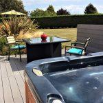 Terrasse exposée sud donnant sur un grand jardin, le jacuzzi et la table extérieur
